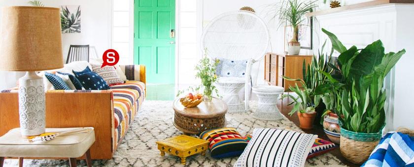 ein wohnzimmer im boho style mit einem hellen teppich und einem bunten sofa auf dem